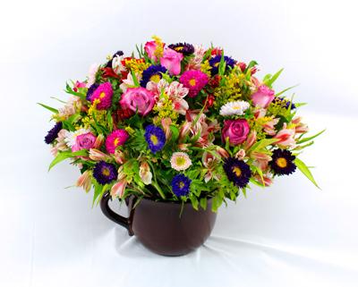 Arreglo floral en un taza de ceramica brillante