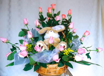 Rosas color pastel en canasta con tierno peluche