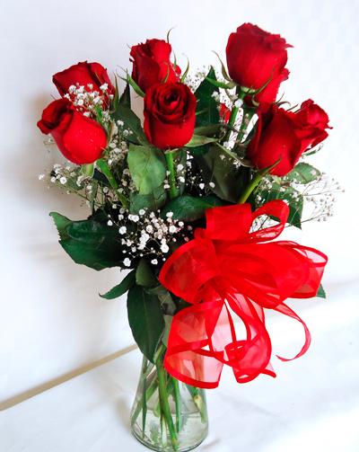 Florero transparente con rosas rojas