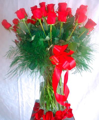 Florero de cristal con mas de dos docenas de rosas